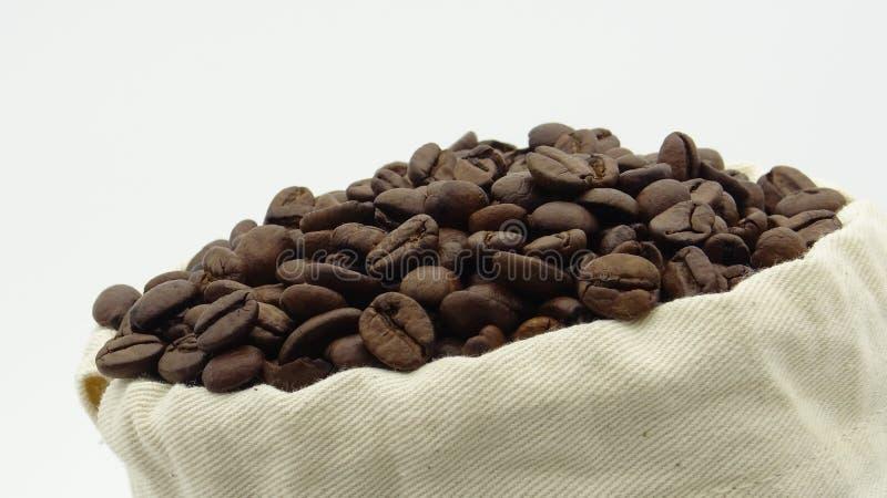 Un saco con los granos de café asados en el fondo blanco foto de archivo libre de regalías