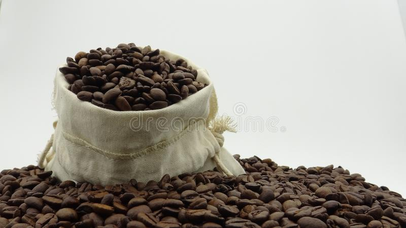 Un saco con los granos de café asados en el fondo blanco fotografía de archivo libre de regalías