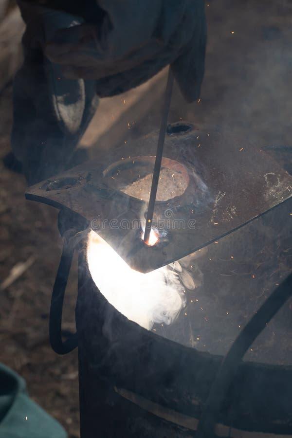 Un saldatore con esperienza sul lavoro Processo di saldatura e della preparazione della fornace del ghisa Fuoco di selezione Prof fotografia stock