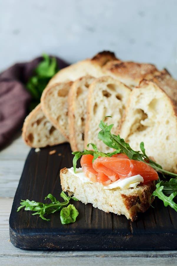 Un sandwich ouvert avec les saumons fumés sur le pain grillé du pain fait maison Bruschette, Smrrebrod images stock