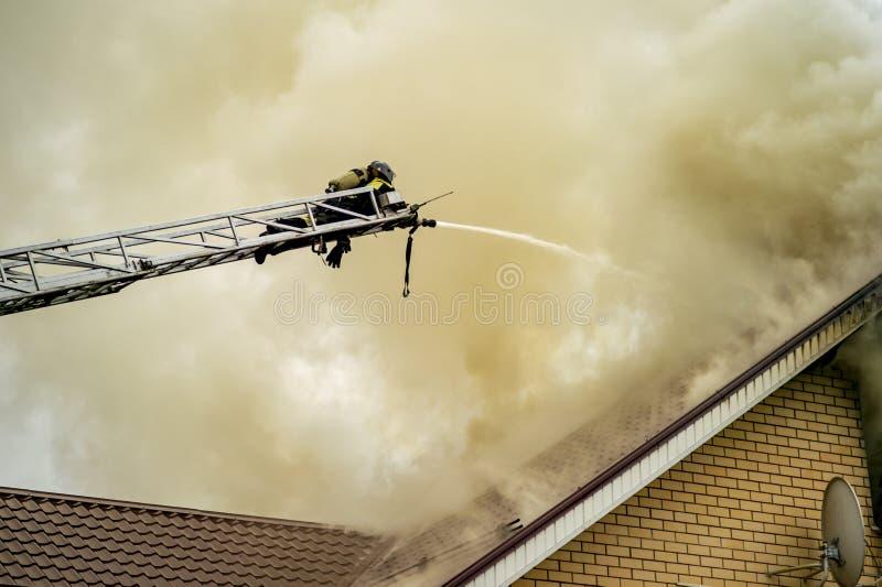 Un sapeur-pompier éteint un bâtiment brûlant avec des échelles d'extension de taille images stock