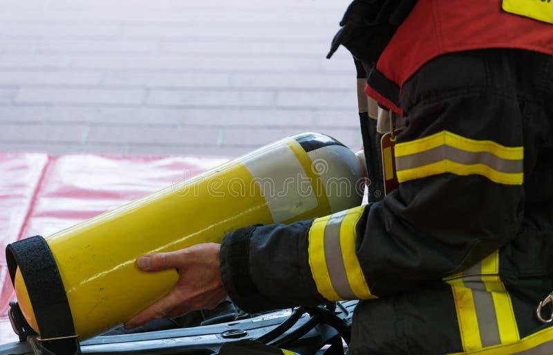 Un sapeur-pompier avec le cylindre d'oxygène photos stock