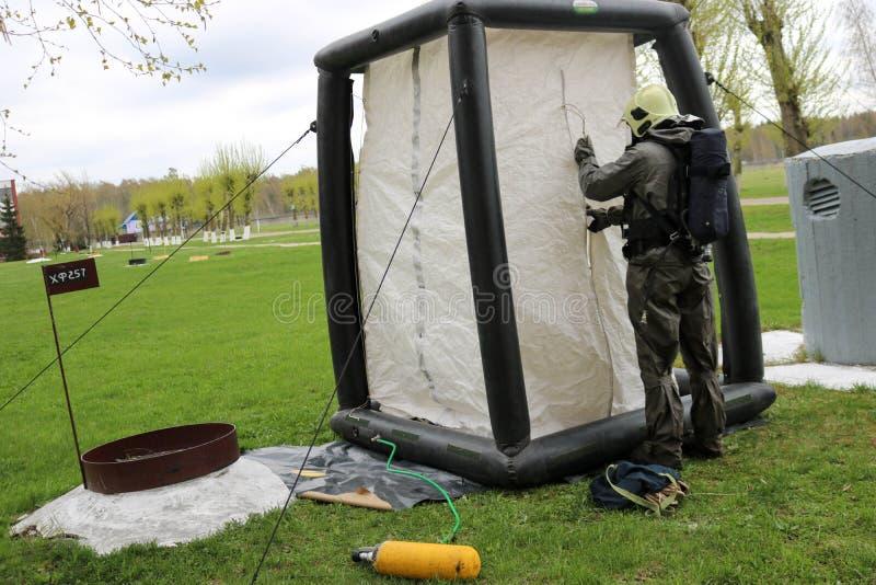Un sapeur-pompier professionnel dans un costume ignifuge spécial noir dispose à assembler une tente blanche de l'oxygène aux pers images libres de droits