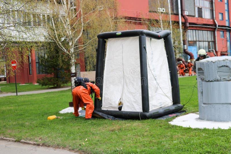 Un sapeur-pompier professionnel dans un costume ignifuge spécial orange dispose à assembler une tente blanche de l'oxygène aux pe photographie stock libre de droits