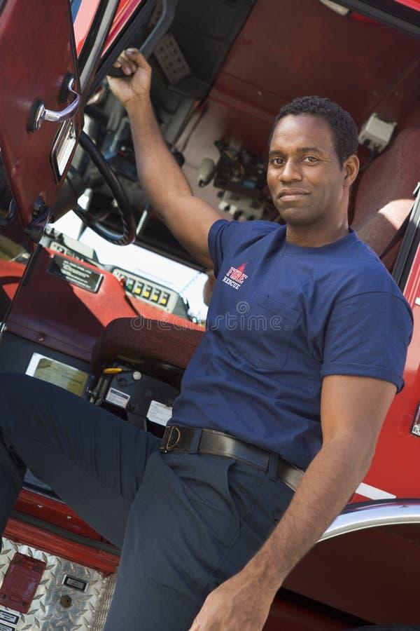 Un sapeur-pompier se tenant prêt le taxi d'une pompe à incendie photo stock