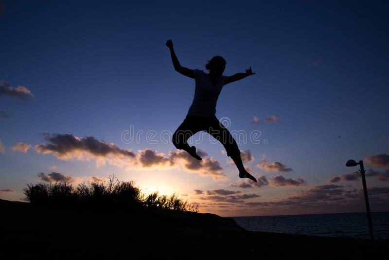 Un saut au coucher du soleil photographie stock libre de droits