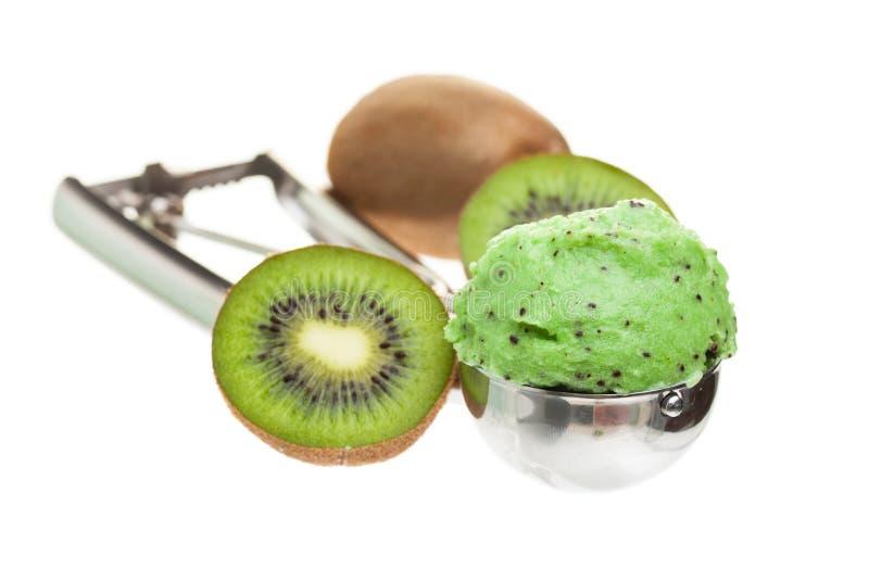 Un scoop de la crème glacée de kiwi d'isolement sur le fond blanc avec la cuillère photographie stock