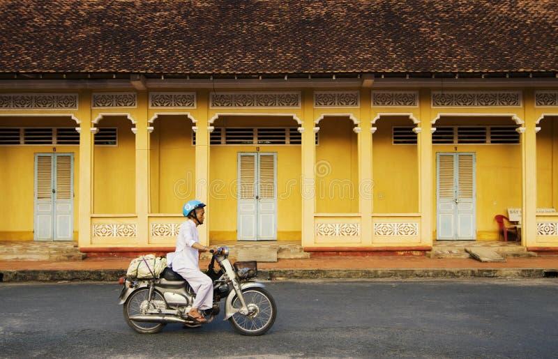 Un scooter d'équitation de femme sur la route rurale en Tay Ninh, Vietnam images stock