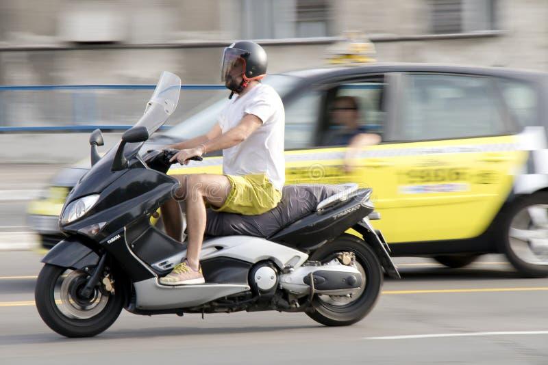 Un scooter d'équitation d'homme dans le trafic de rue de ville image libre de droits