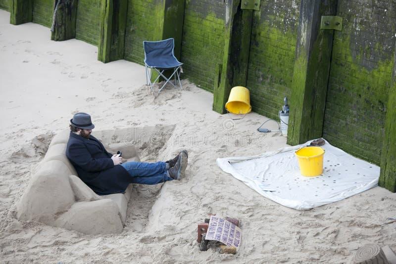 Un sculpteur crée le sable de sofa tandis que la marée est sur la rive sud de la Tamise à Londres centrale, R-U images stock