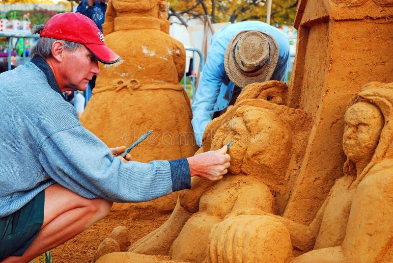 Un sculpteur de sable travaillant à sa création photos stock