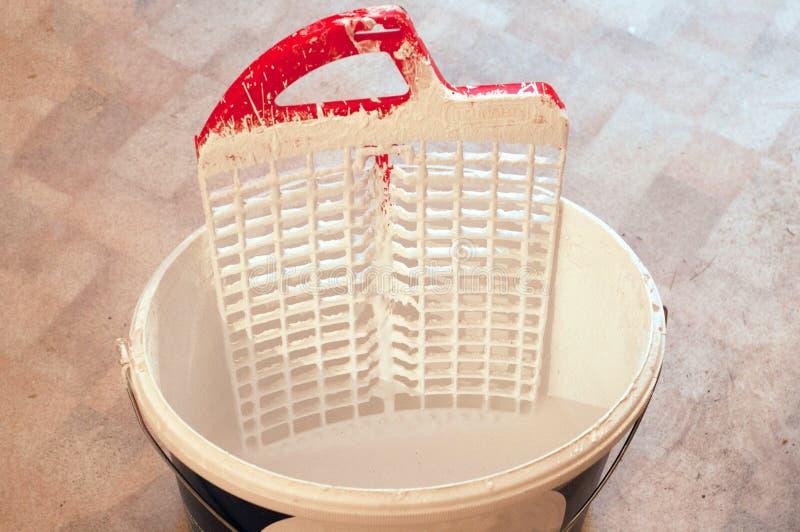 Un seau avec la peinture à émulsion de l'eau blanche avec des plateaux de peinture sur le plancher de PVC photo stock