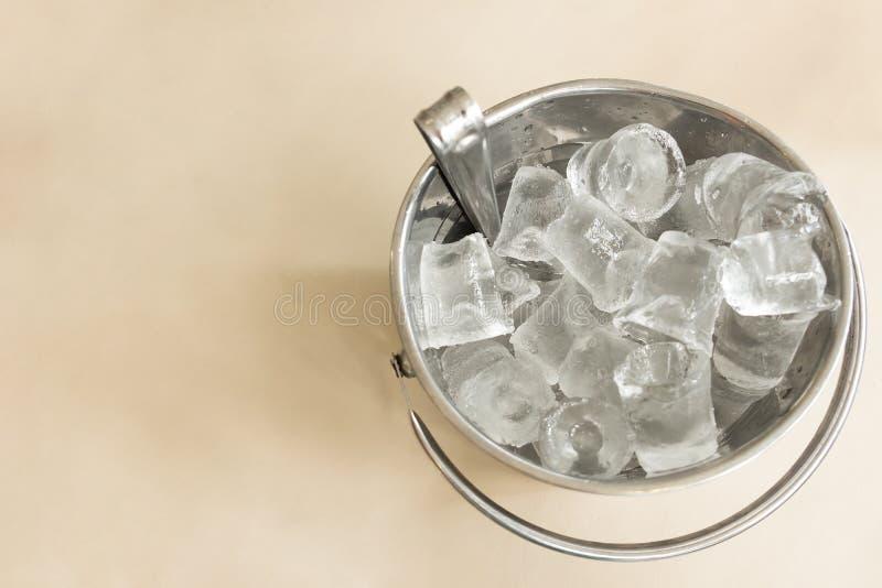 Un secchio d'argento fatto da alluminio in pieno riempito di cubetto di ghiaccio è disposto sulla tavola al pub, ghiaccio è stato immagine stock libera da diritti