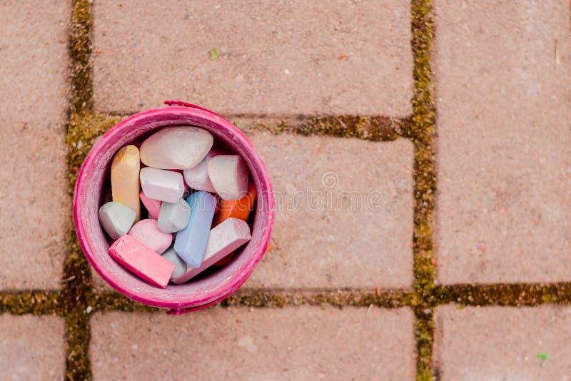 Un secchio di gesso variopinto sull'asfalto in scatola di plastica Disegnando con il gesso sulla pavimentazione pastelli multicol fotografia stock libera da diritti