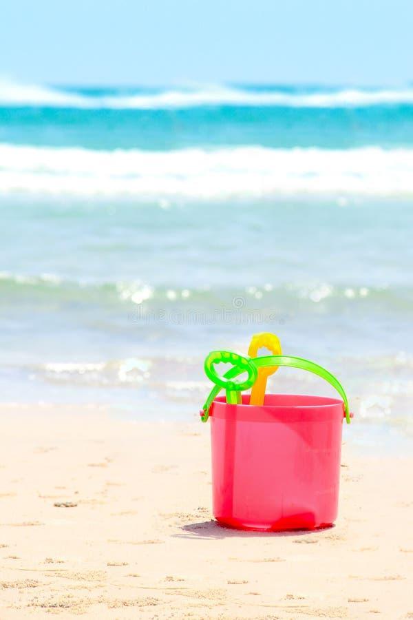 Un secchio e giocattoli della sabbia per il gioco di bambini alla spiaggia fotografia stock libera da diritti