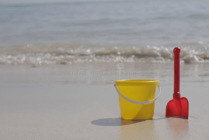 Un secchio giallo del bambino e un supporto rosso della pala sulla sabbia dal mare immagini stock