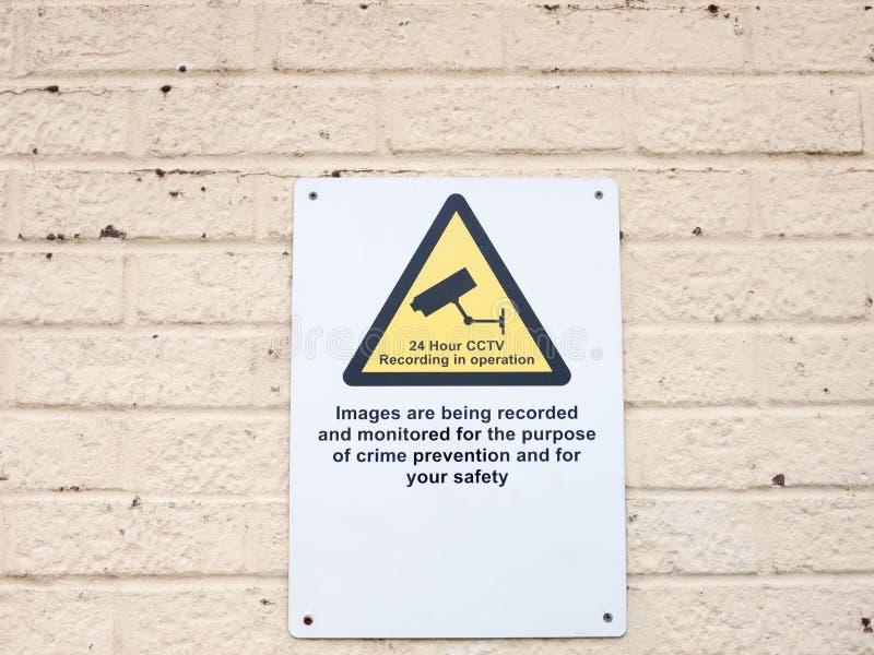 Un segno bianco del cartello su avvertimento del cctv di sorveglianza della parete fotografie stock libere da diritti