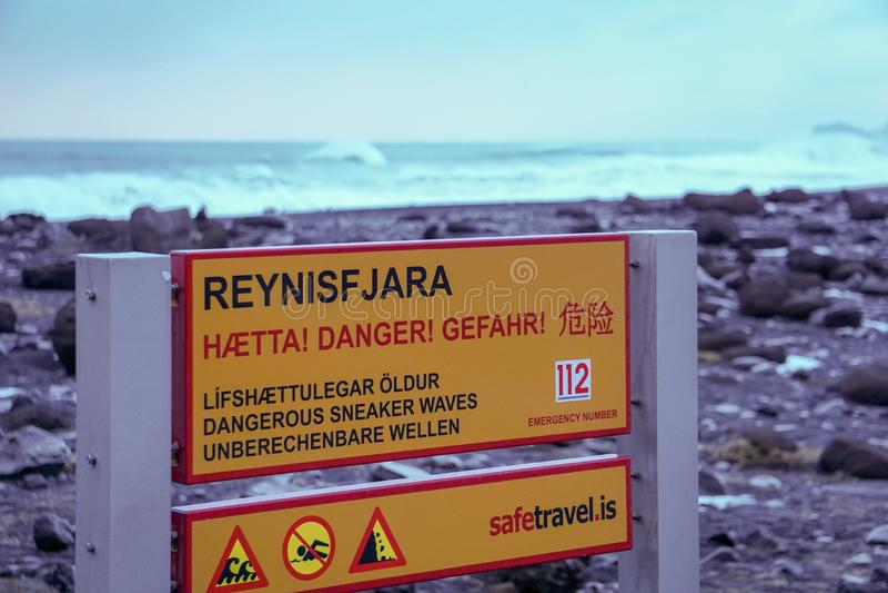 Un segno che informa circa i pericoli sulla spiaggia di Reynisfjara, con le onde fracassanti nei precedenti fotografie stock