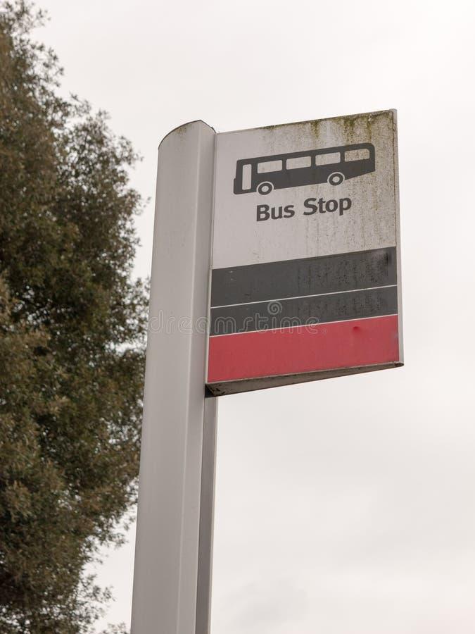Un segno della fermata dell'autobus con un'icona del bus bianca e nera e rossa immagine stock