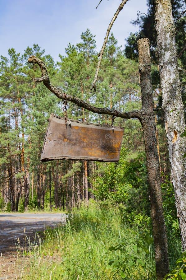 Un segno di legno sulle catene appende su un ramo di albero immagine stock