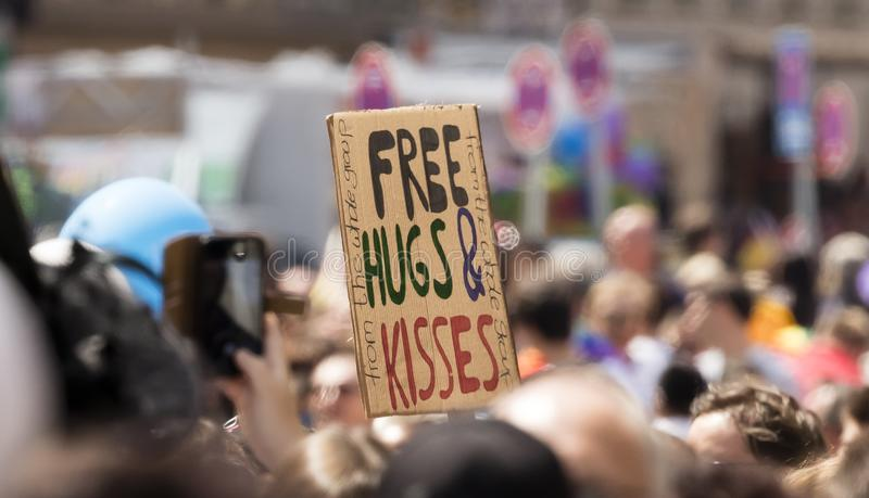 """Un segno fuori con un titolo """"abbracci e baci liberi dall'intero gruppo """", visualizzato alla parata di Gay Pride a Monaco di Bavi immagini stock libere da diritti"""
