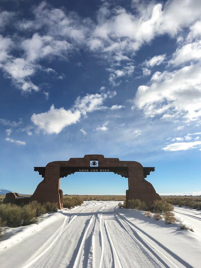 Un segno sopra un arco dell'adobe che dice nel ` spagnolo va con il ` di Dio fotografie stock libere da diritti