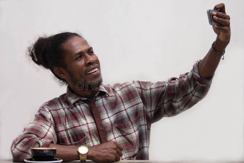 Un selfie di conversazione del giovane uomo di colore con il telefono e sorridere in camera, selfie di attimo di sorriso del giov immagini stock libere da diritti