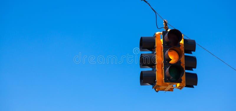 Un semáforo amarillo con un fondo del azul de cielo fotografía de archivo libre de regalías