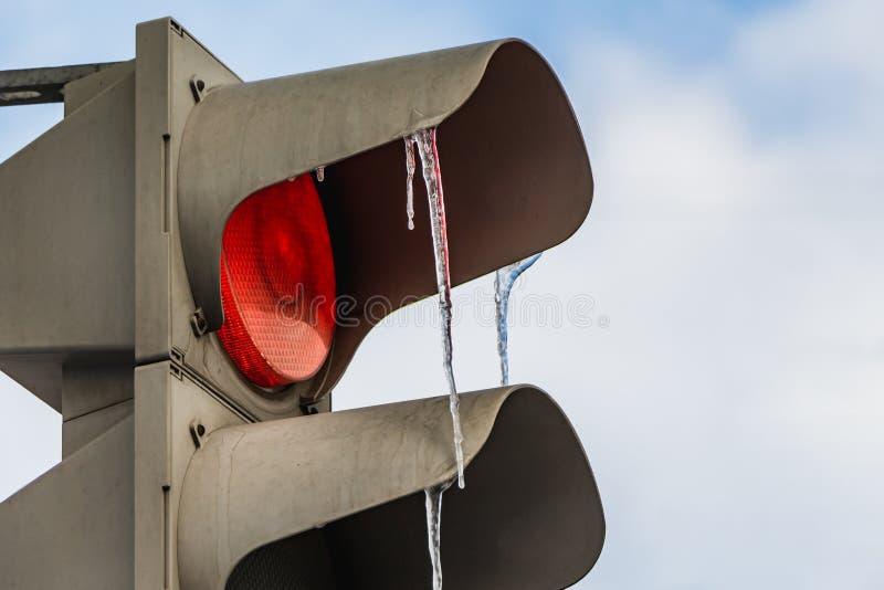 Un semáforo metálico gris del diod con la luz roja del LED encendido y un grupo de carámbanos coloreados transparentes en el fond fotos de archivo libres de regalías