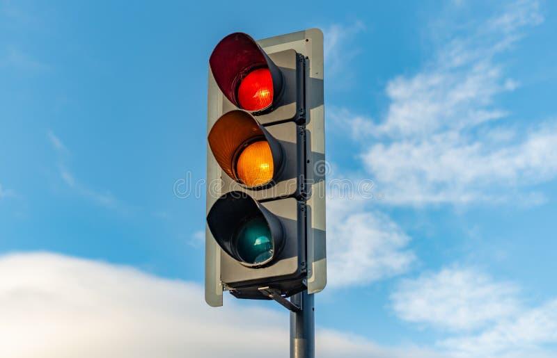 Un semaforo inglese si siede contro un cielo blu luminoso fotografia stock