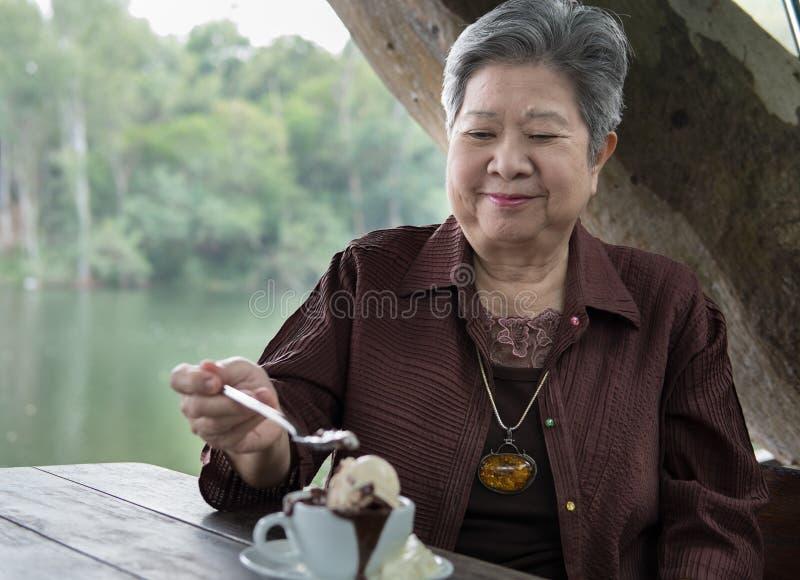 Un senoir plus ancien mangeant le gâteau et la glace à la vanille de lave de chocolat à c images stock