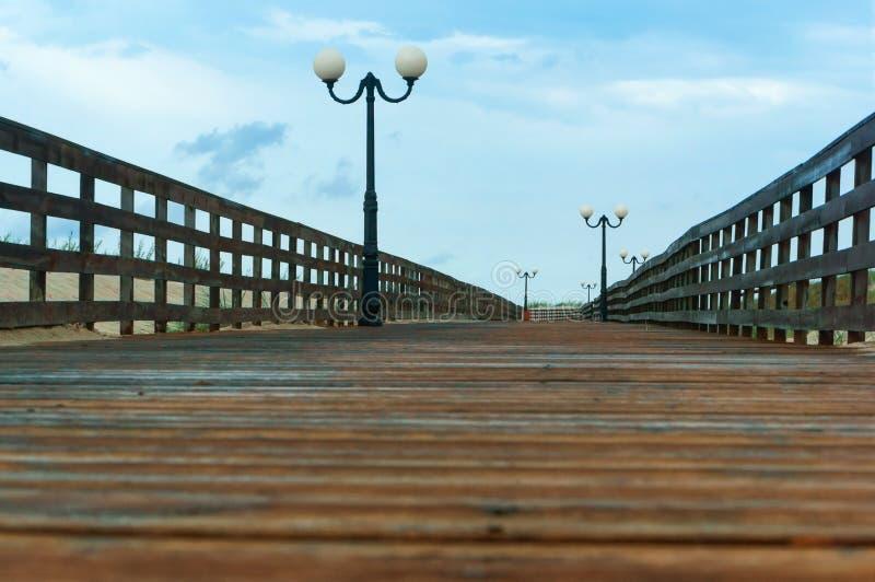 Un sentiero costiero di legno con le luci, piattaforma di legno con le inferriate immagine stock libera da diritti