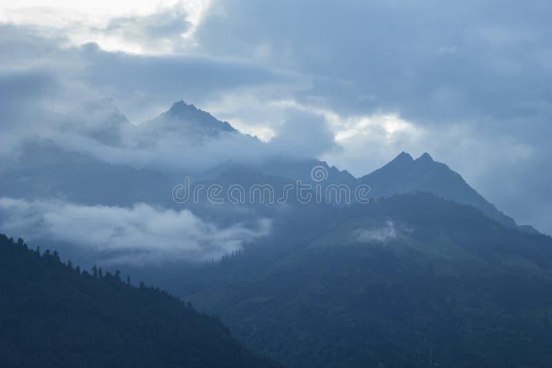 Un sera tardi nelle siluette nebbiose delle montagne fotografia stock