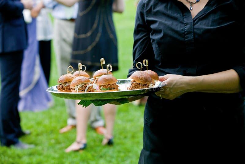 Un server che tiene un vassoio in pieno di mini panini tirati della carne di maiale durante l'evento approvvigionato fotografia stock libera da diritti