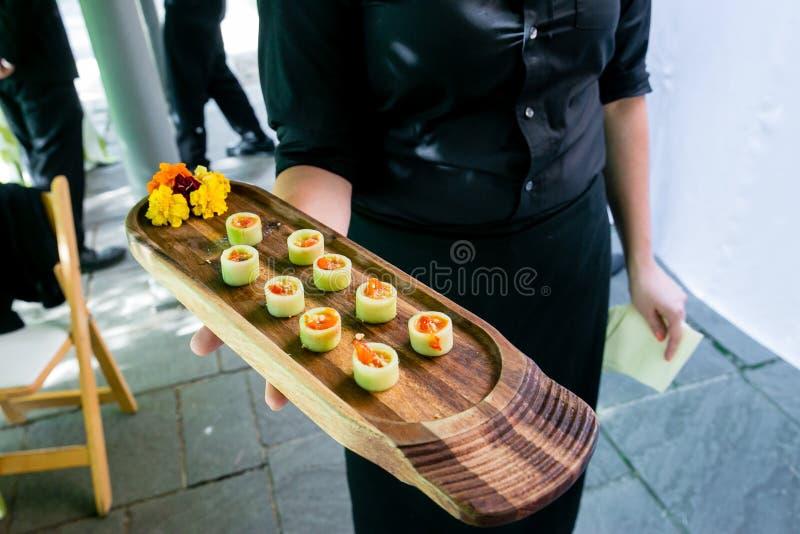 Un serveur tenant un plateau en bois complètement des apéritifs végétariens - épouser la série de restauration photos libres de droits