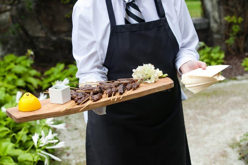 Un servidor que sostiene una bandeja de madera por completo de bocados de la carne durante un acontecimiento abastecido fotos de archivo libres de regalías