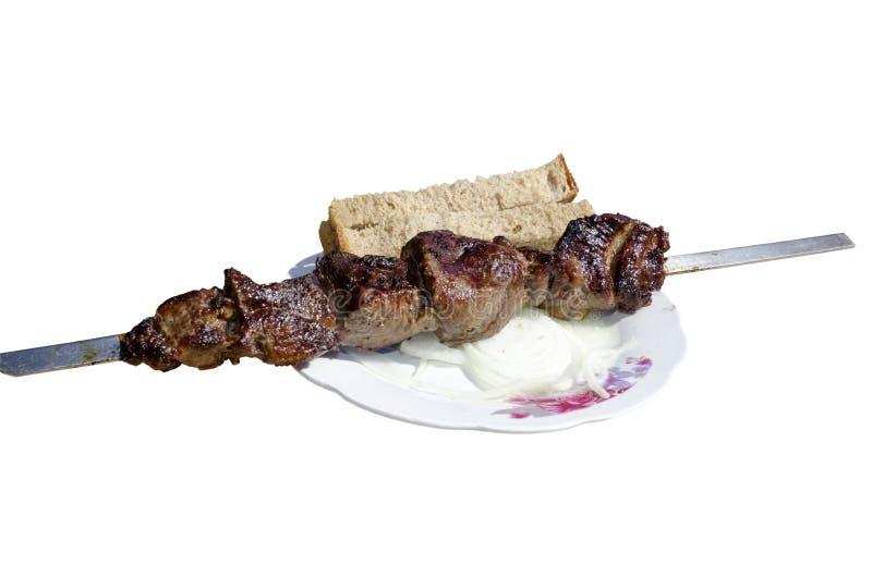 Un shashlik prêt avec des oignons et du pain sur l'assiette photos libres de droits
