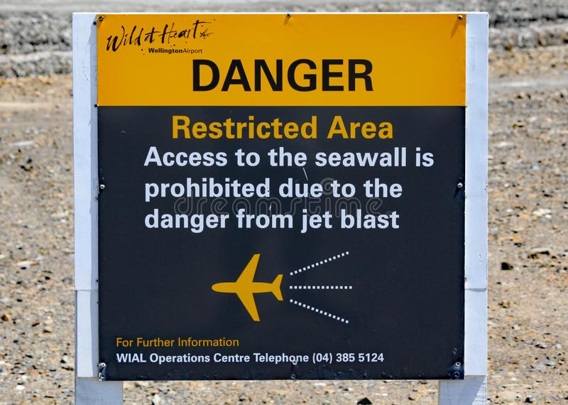Un signe à l'extrémité de la piste d'aéroport à Wellington, le Nouvelle-Zélande, l'avertissement des dangers du souffle de jet et photographie stock libre de droits