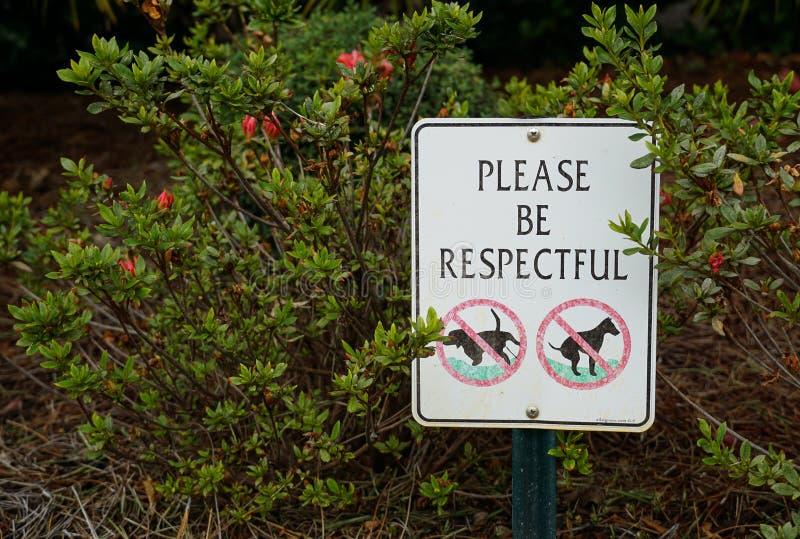Un signe avec des buissons à l'arrière-plan photo stock
