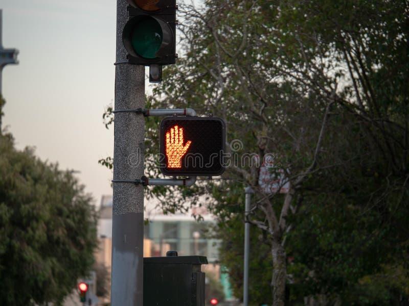 Un signe piétonnier d'arrêt apparaît sur un passage piéton image stock