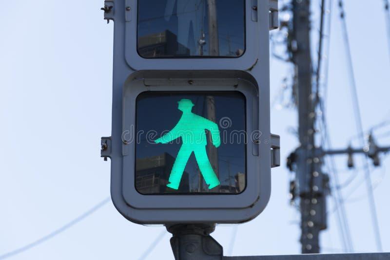 Un signe vert de feu de signalisation qui indique des personnes peut marcher ou marche de piéton Ce poteau de signalisation était image libre de droits
