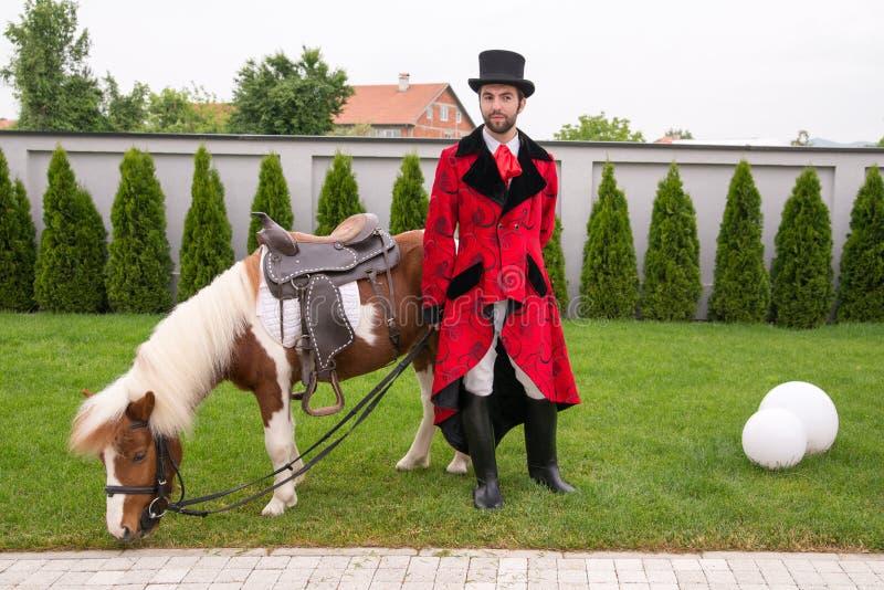 Un signore con una barba in un vestito di guida che posa per una foto che pende contro un cavallo immagine stock libera da diritti