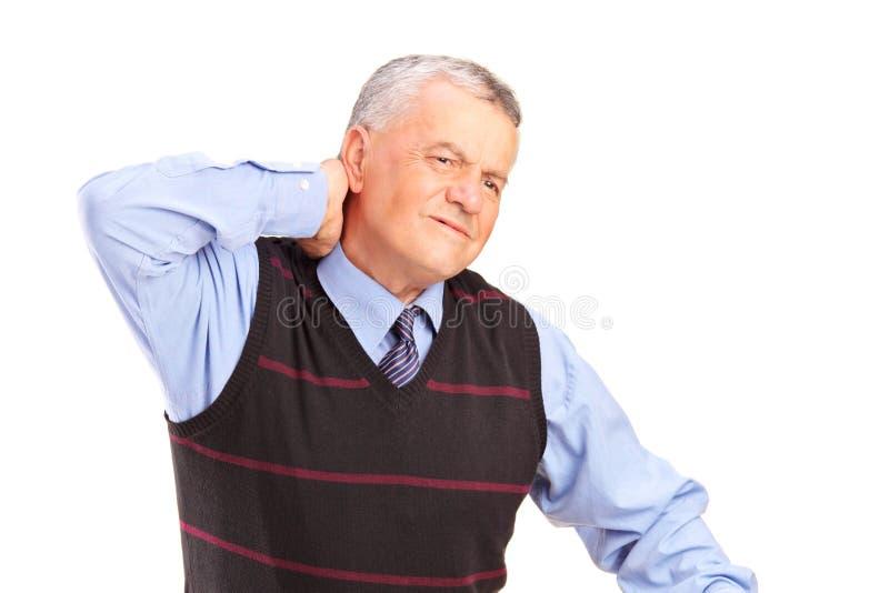 Un signore maturo che soffre da un dolore al collo fotografia stock libera da diritti