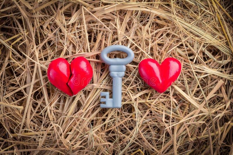 Un simbolo di due cuori con la chiave rossa immagini stock