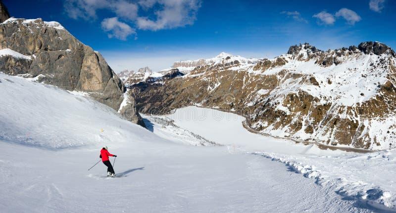 Un singolo sciatore sul supporto Marmolada che si avvicina al lago Fedaia, dolomia, Italia immagine stock