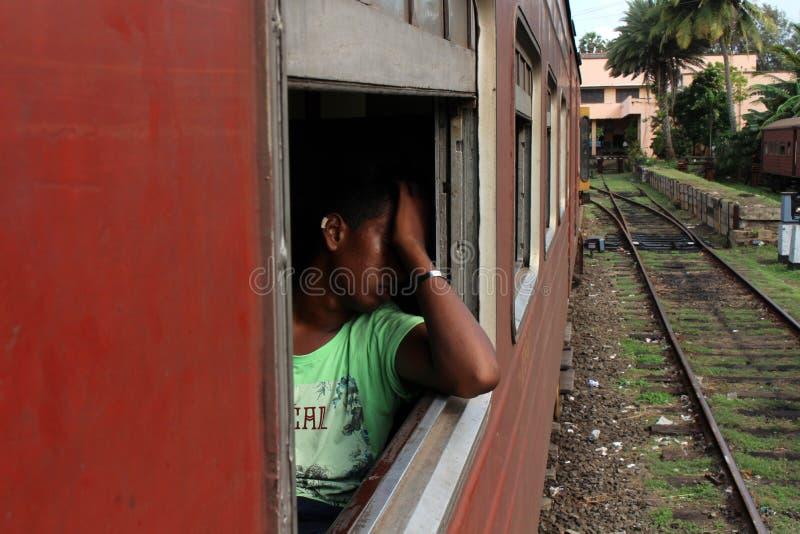 Un Sinhalese local parece cansado en un tren de Galle a Colombo foto de archivo libre de regalías