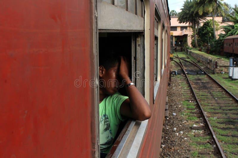 Un Sinhalese local parece cansado en un tren de Galle a Colombo fotos de archivo