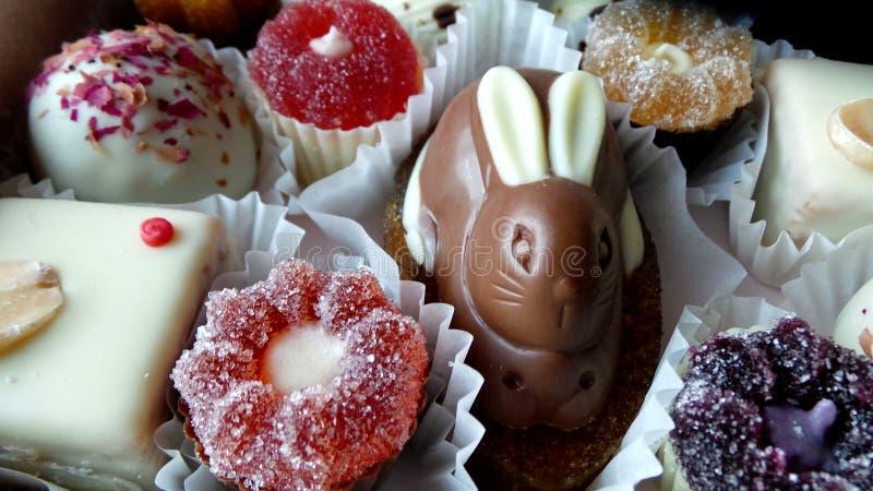 Un sistema de caramelos de la mermelada y de chocolate con una figura del conejo imagenes de archivo