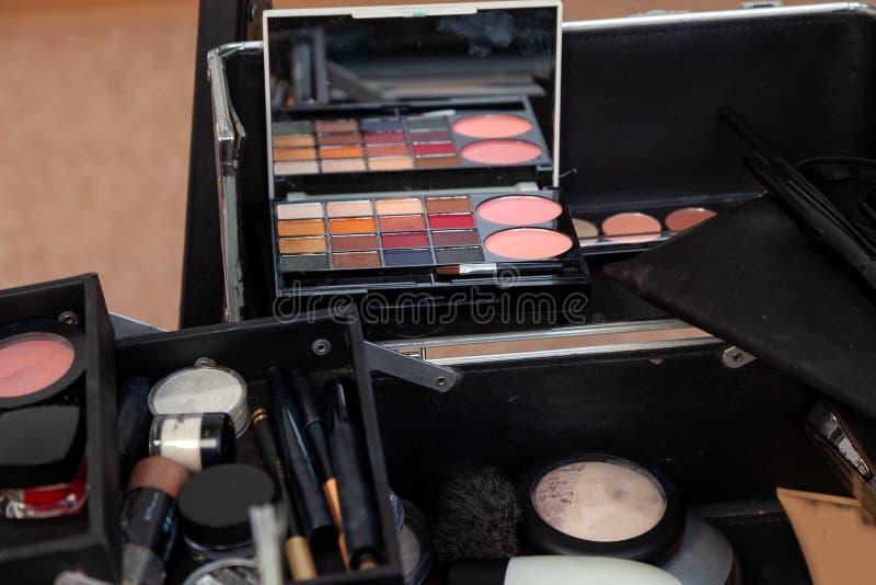 Un sistema de cosméticos profesionales en el cierre abierto de la caja para arriba con el contenido en el estudio del rostro, dia foto de archivo