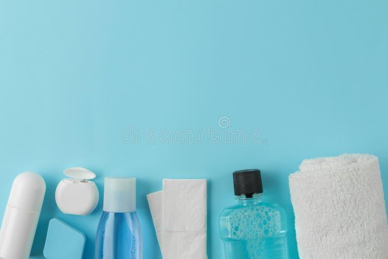 Un sistema de cosméticos y de productos del cuidado personal para viajar en un fondo azul claro apacible Visi?n superior cosmétic fotos de archivo